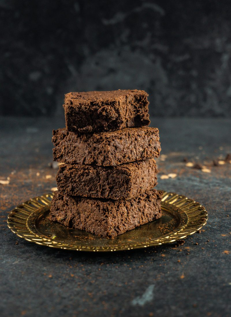 Vegan and Gluten-free Zucchini Brownies stacked on a small gold plate with the top one missing a bite, placed in the middle