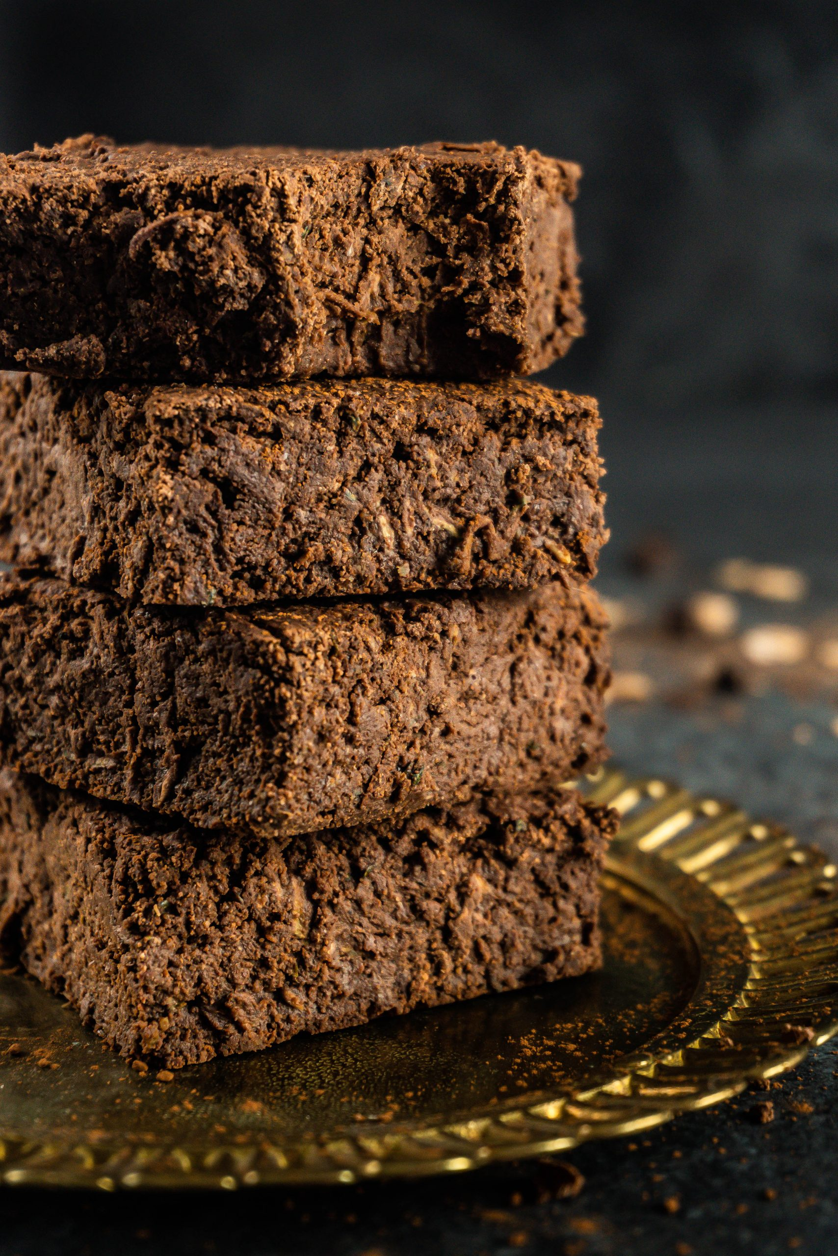 Vegan and Gluten-free Zucchini Brownies stacked on a small gold plate with the top one missing a bite, photographed up close