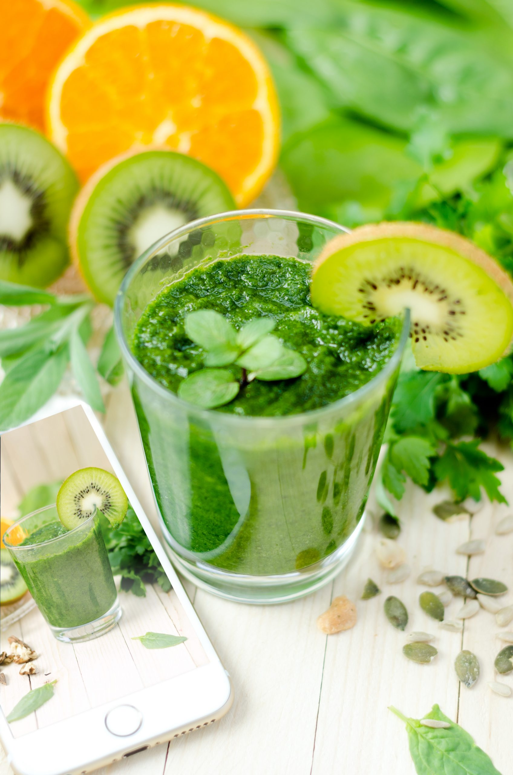 Green juice with a kiwi stuck into it and more green vegetables visible in the background