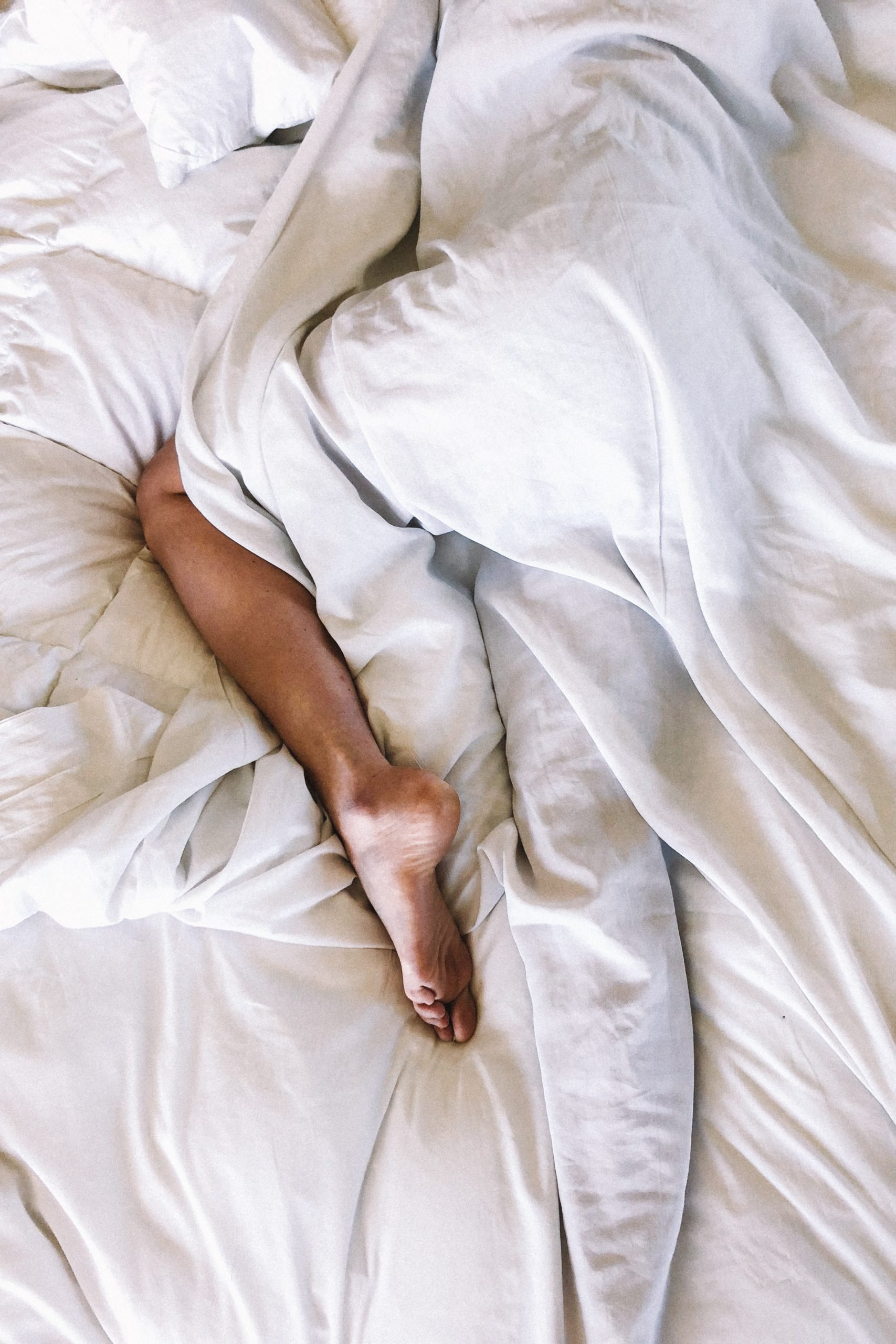 One leg sticking out of the covers