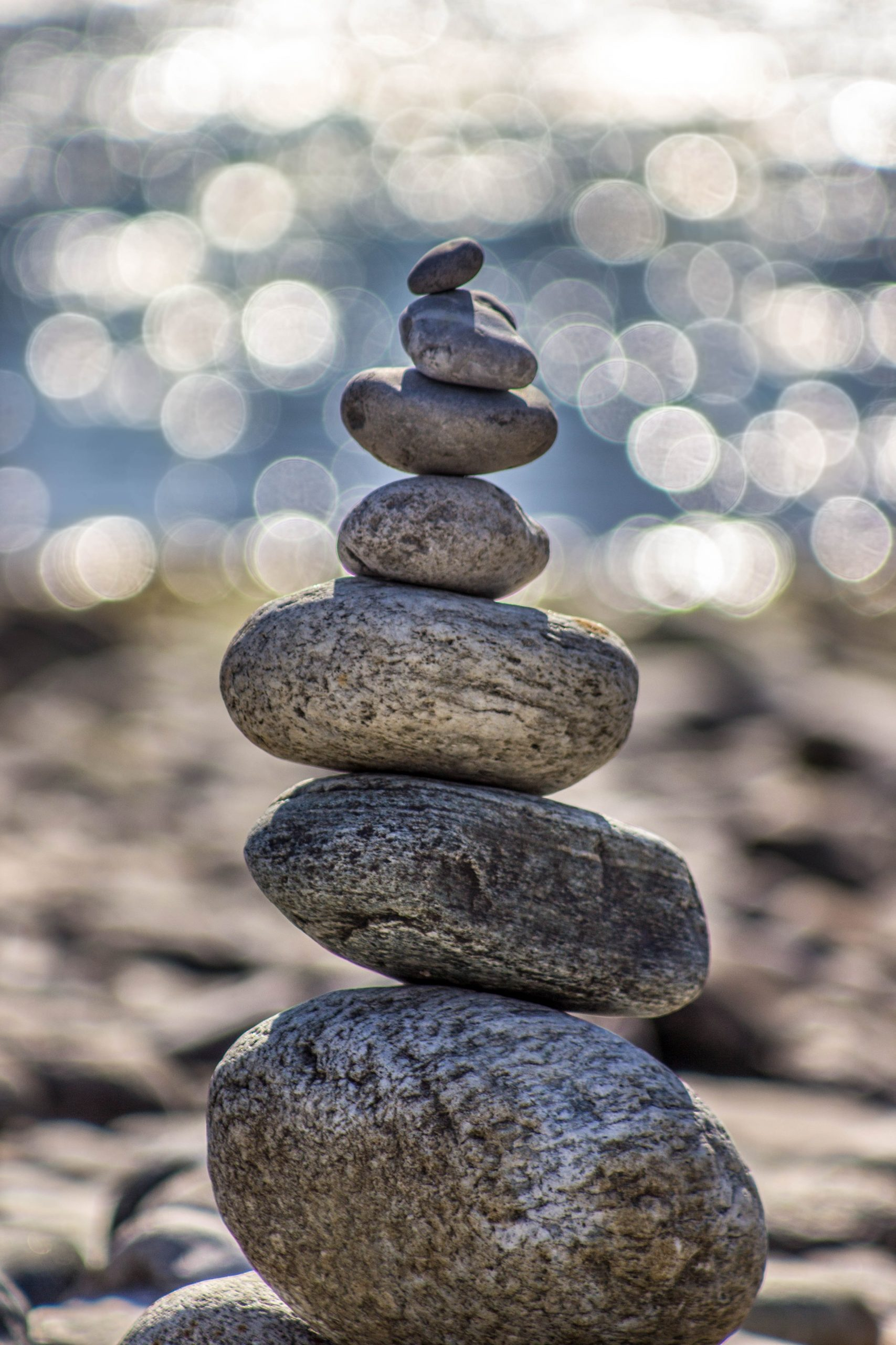Stones balancing on one another with the sea shore in the background