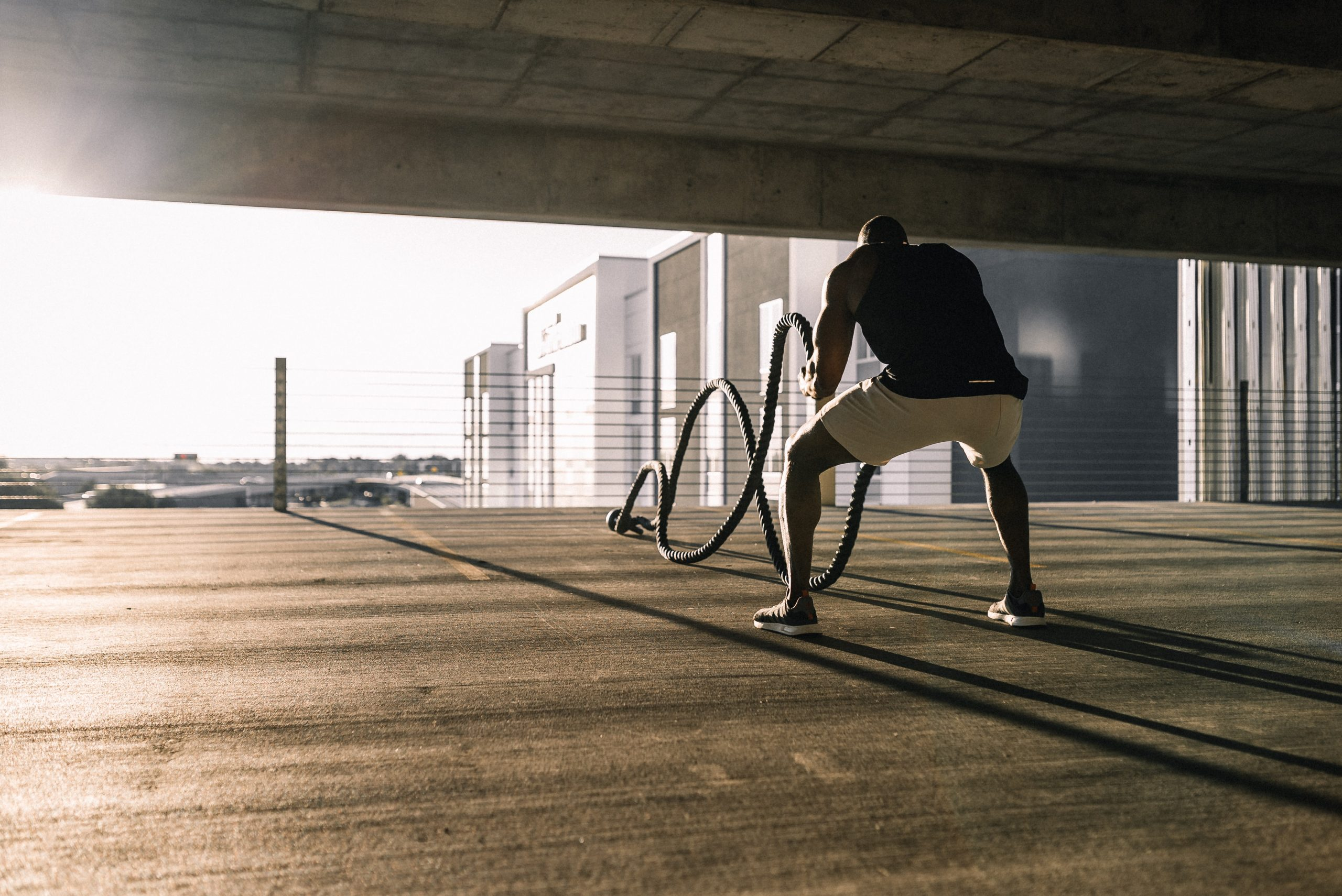 Man exercising with ropes in a parking lot