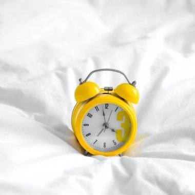 Yellow alarm clock on white sheets
