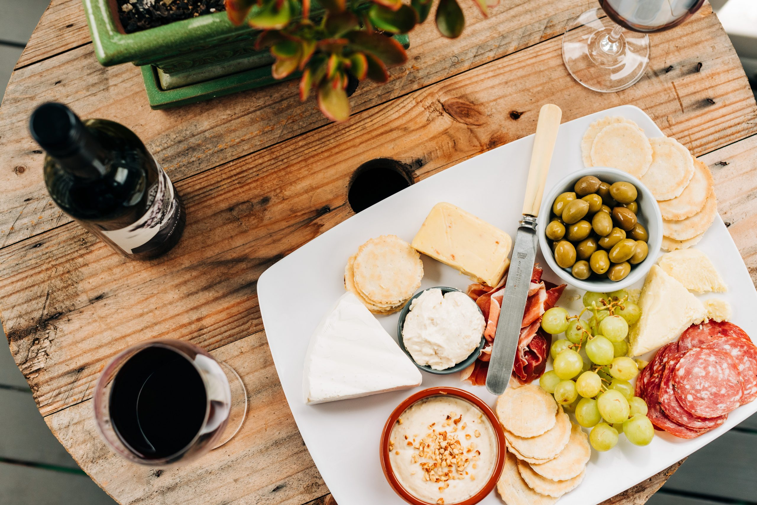 Charcuterie board with meats, olives, cheeses, and wine