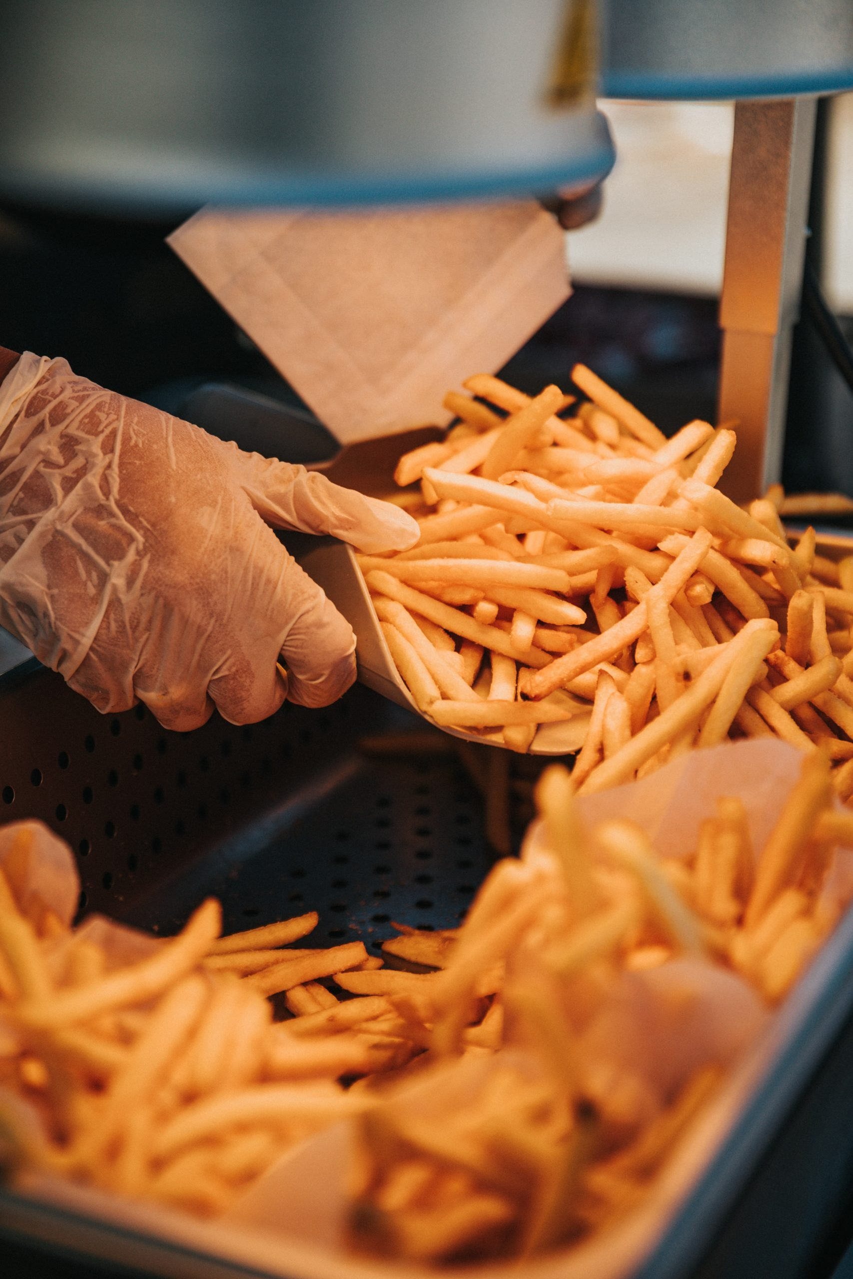 French fries being pulled out of a hot keeping holder