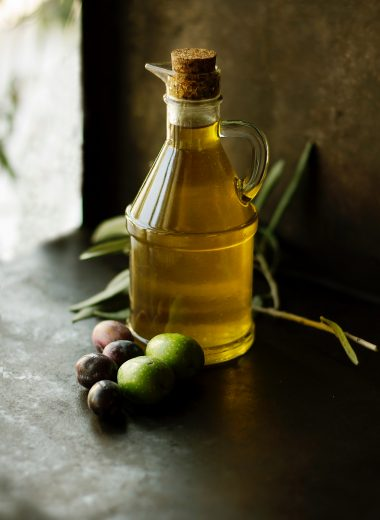 Jar of olive oil surrounded by olives