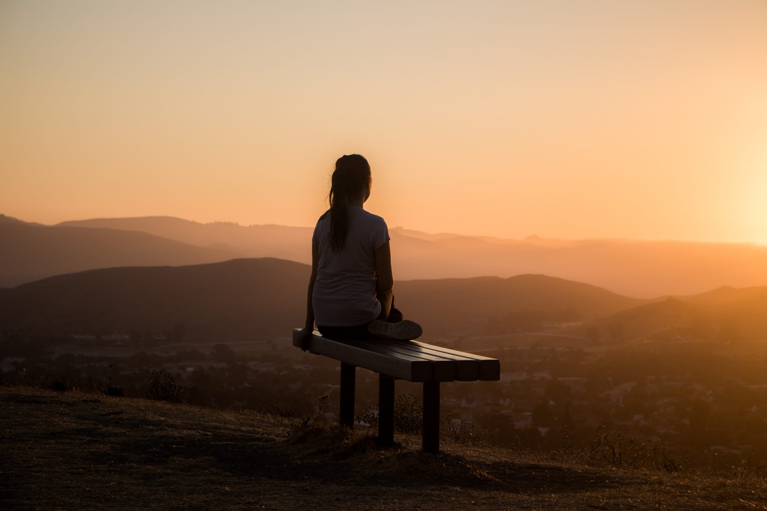 Woman sitting on a bench overlooking a sunrise in the mountains