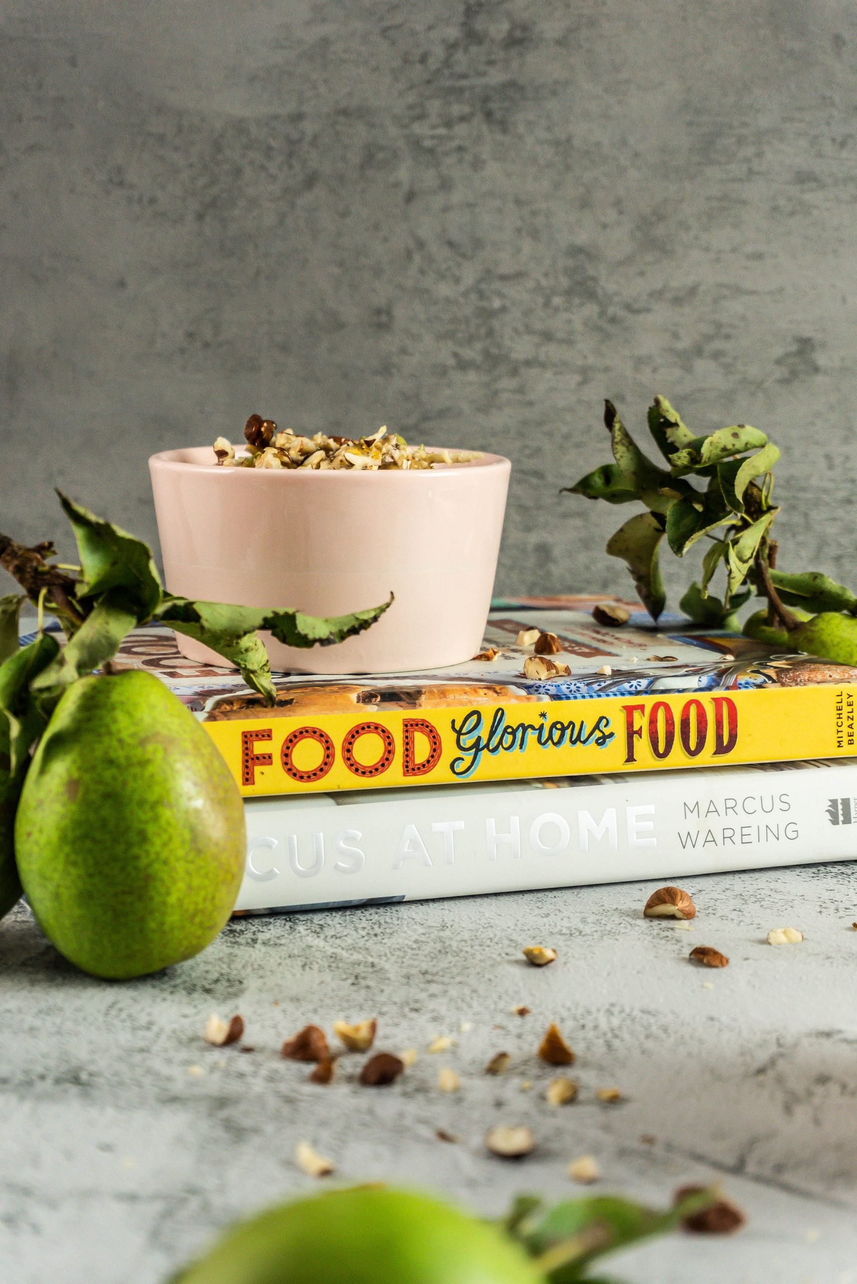 Bircher Muesli with pears and hazelnuts stacked on some books, surrounded by pears