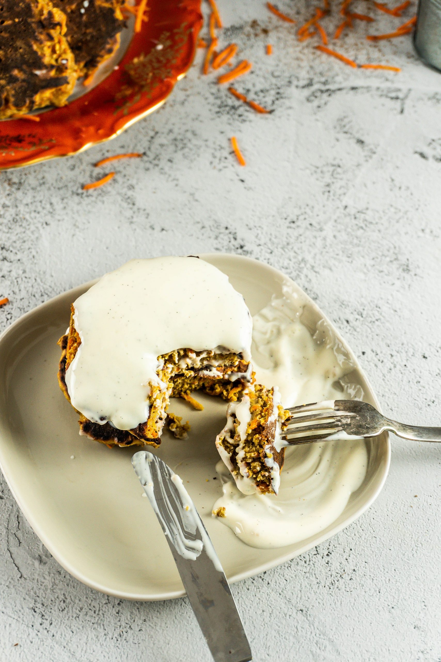 Carrot Cake Pancakes with a Vanilla icing on a small plate covered in icing with a knife and fork stuck into it