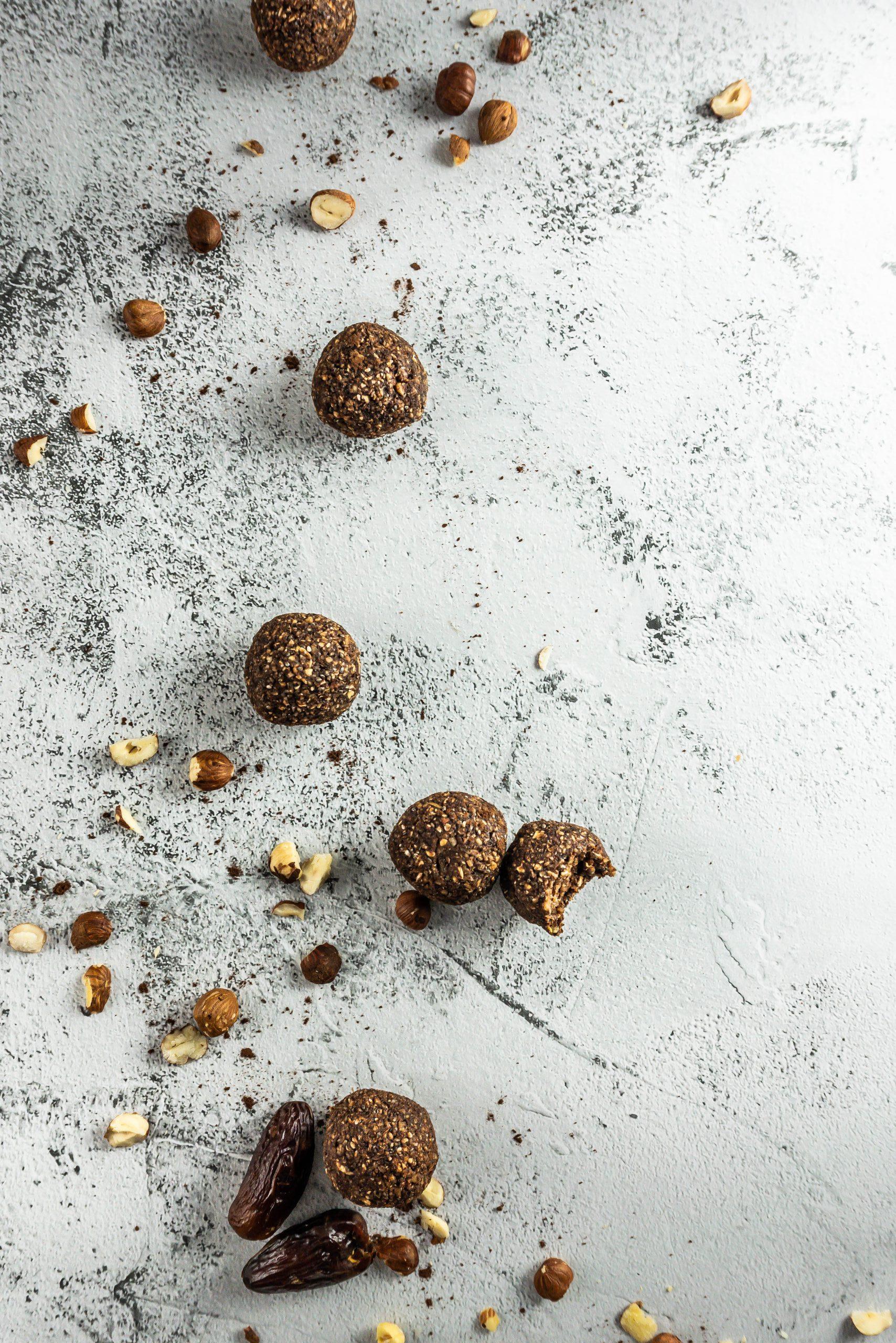 Chocolate Hazelnut Energy Balls on a concrete background with chopped hazelnuts lying around