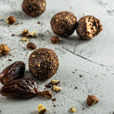 Chocolate Hazelnut Energy Balls in focus surrounded by dates and chopped hazelnuts