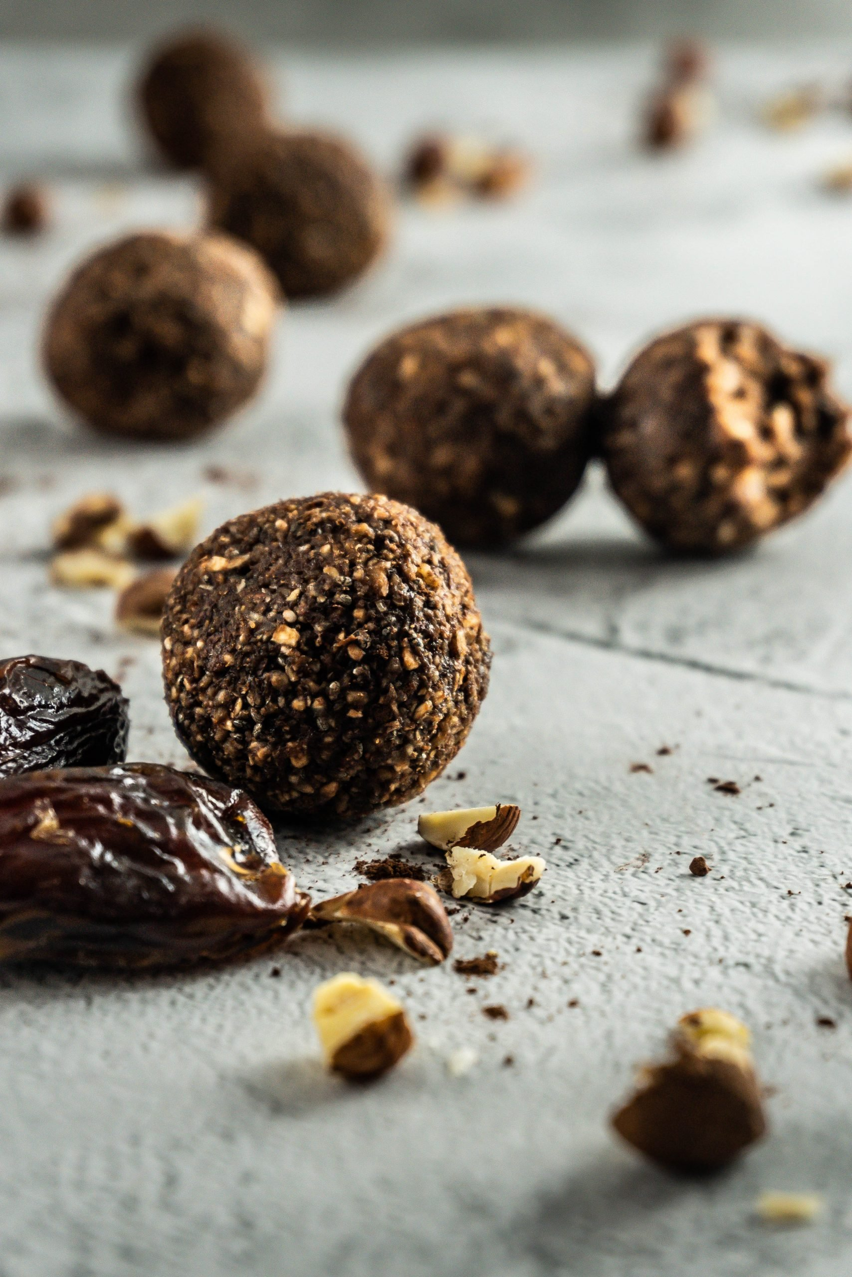 Chocolate Hazelnut Energy Ball in focus surrounded by dates and chopped hazelnuts