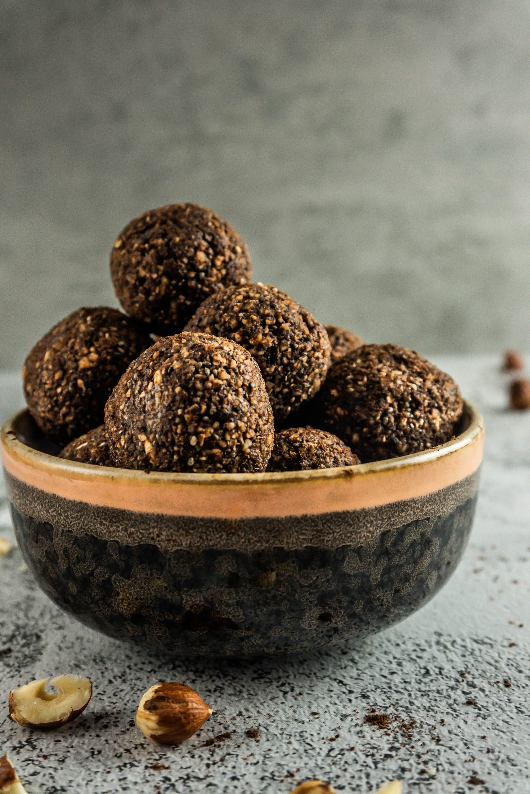 Chocolate Hazelnut Energy Balls in a bowl with chopped hazelnuts scattered around. Photographed from a side angle