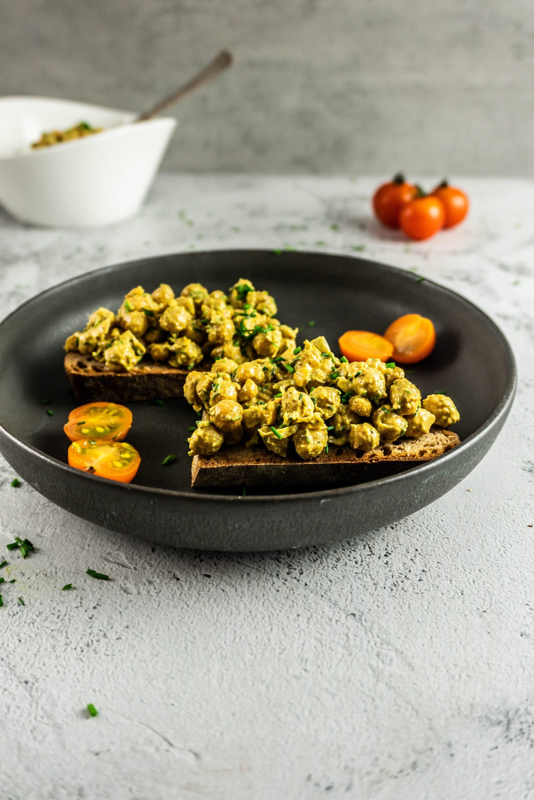 Vegan Curried Chickpea Spread on a dark plate with chopped chives and tomatoes visible in the background