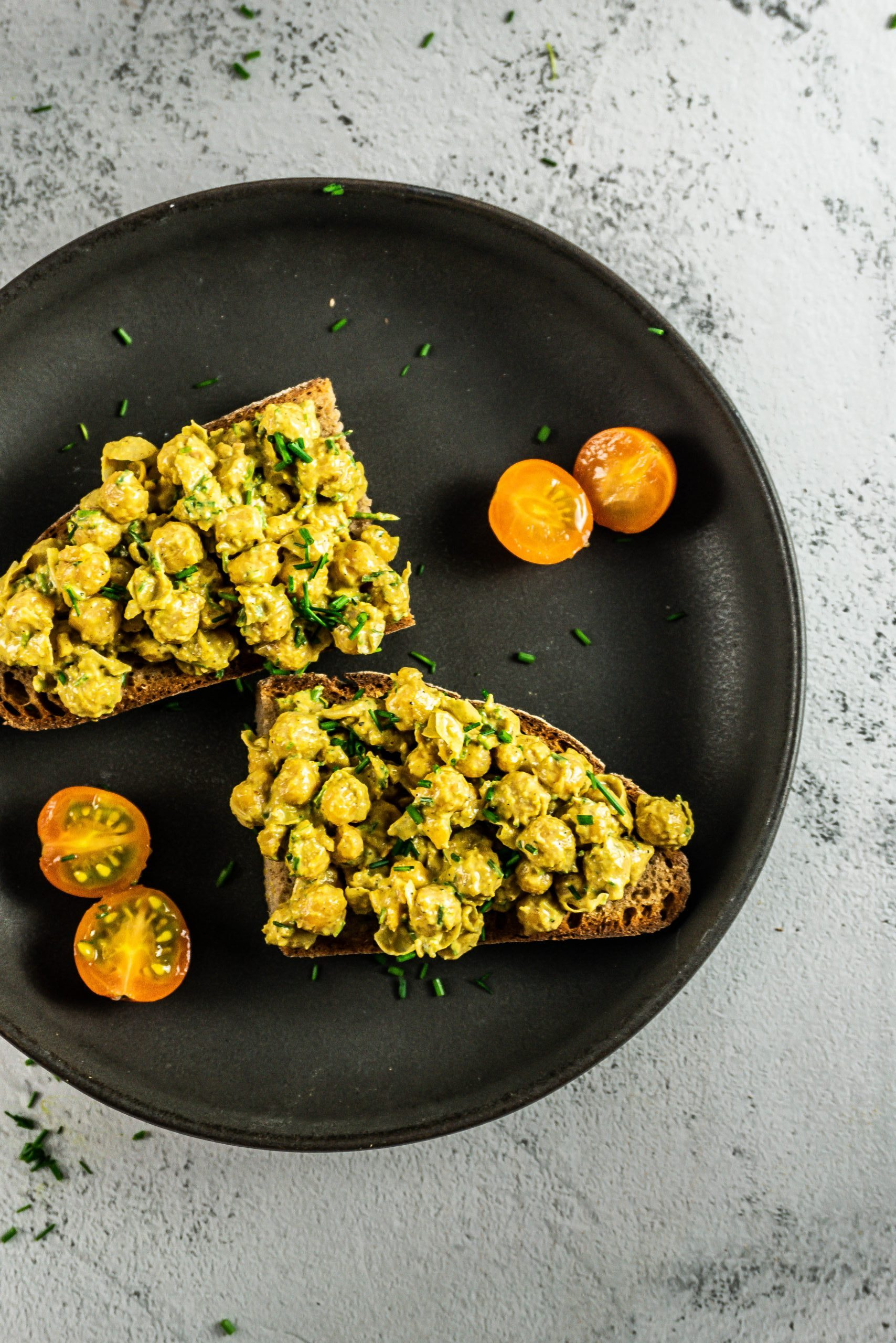Vegan Curried Chickpea Spread on a slice of bread photographed on a dark plate