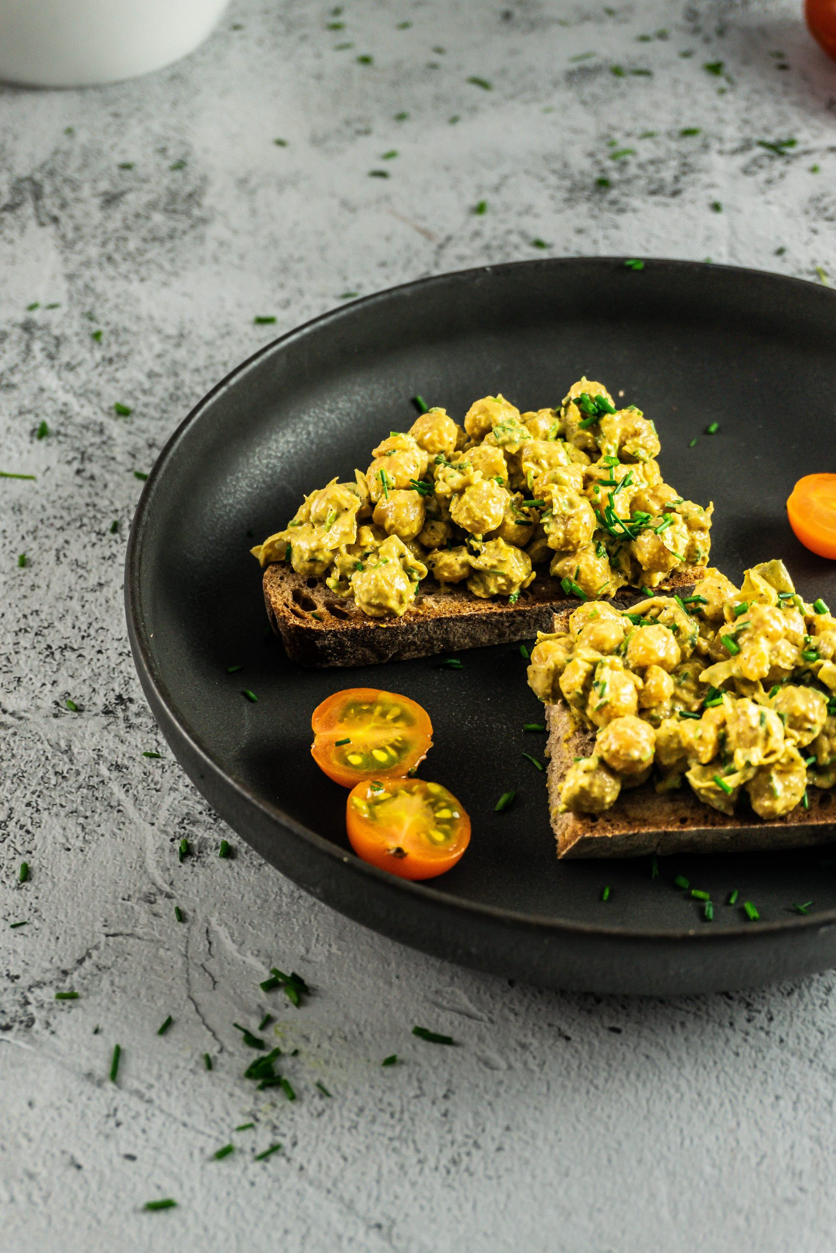 Vegan Curried Chickpea Spread on a dark plate with chopped chives and tomatoes visible in the background, photographed from a three-quarter angle