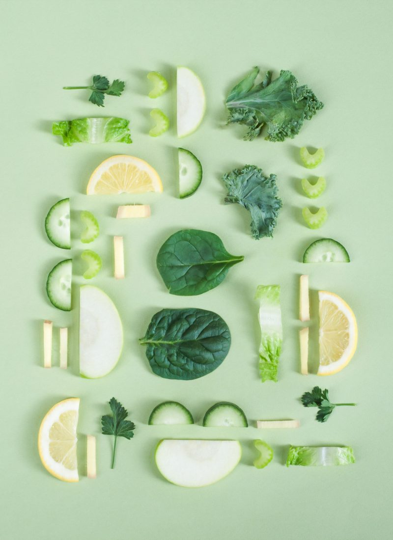 Spinach, apple, cucumber, lettuce, lemon, and celery on a green board