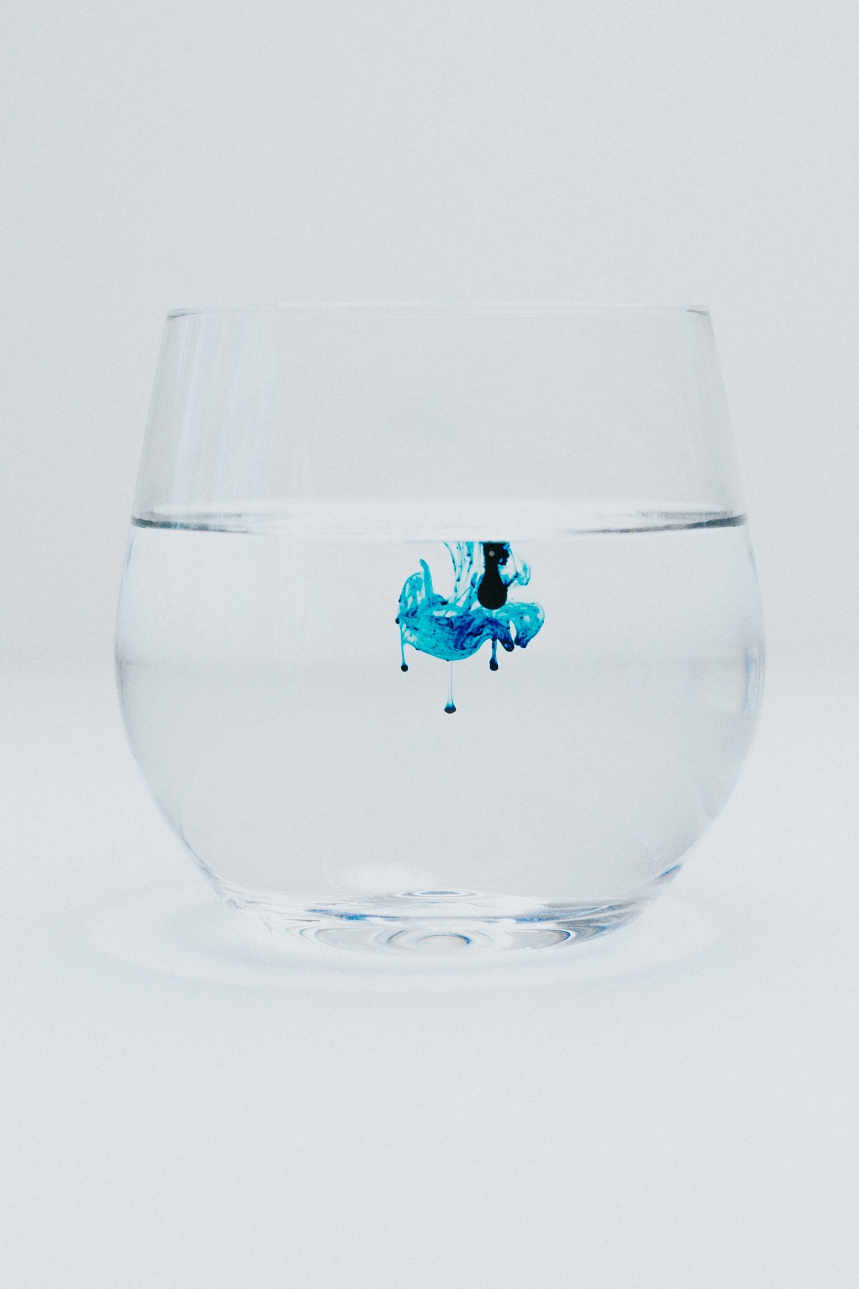 A drop of blue die in a water glass on a pure background