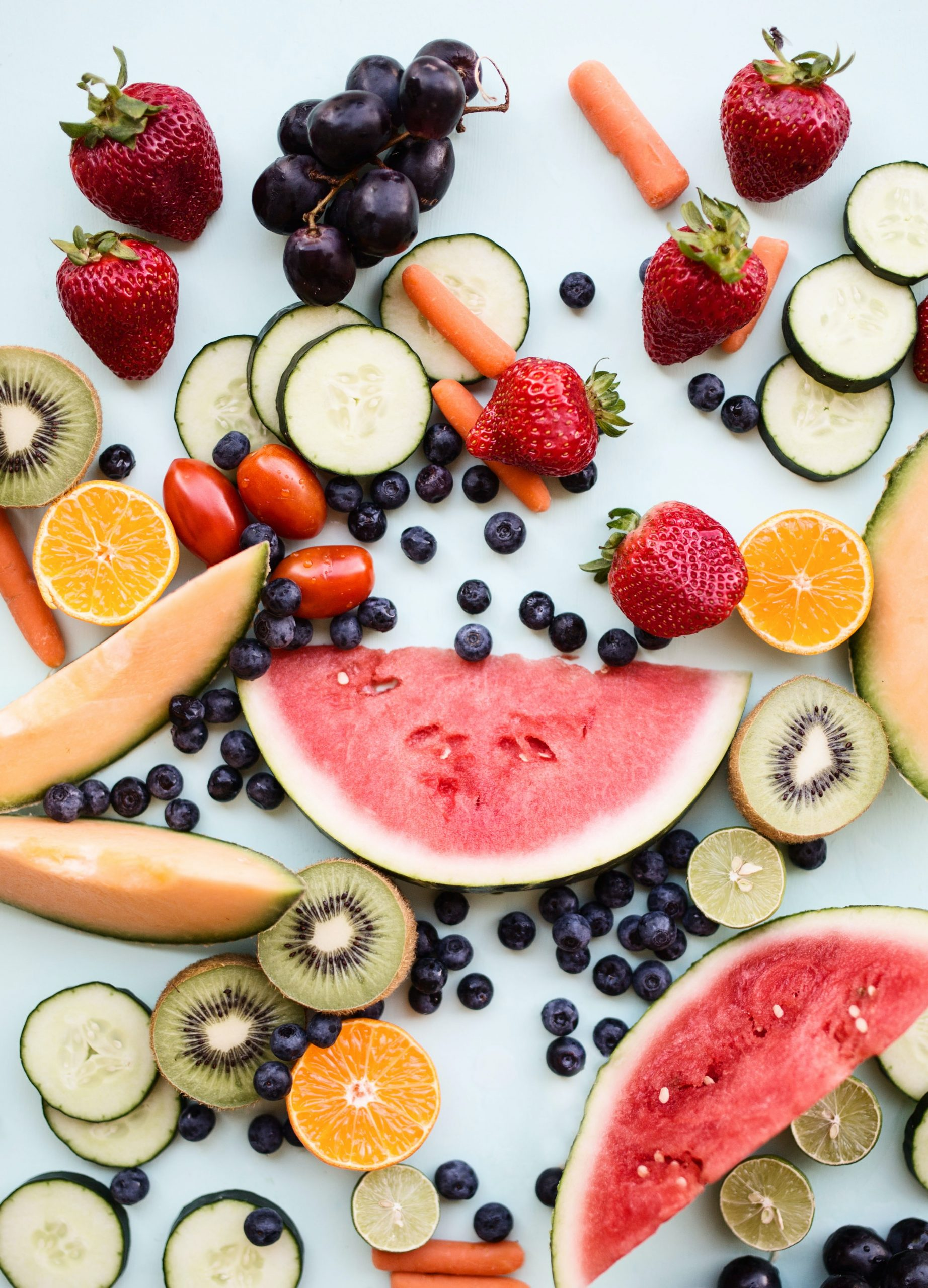 Slices of watermelon, strawberries, cucumbers, and blueberries