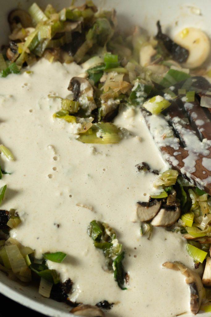 Adding cashew cream to roasted garlics, leeks, mushrooms, and sun-dried tomatoes