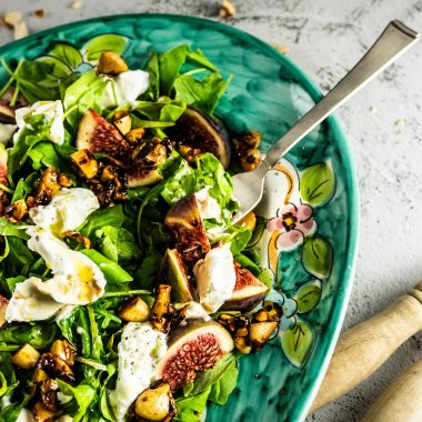 Fig and Arugula Salad with Buffalo Mozzarella on a colorful plate with a fork tugged into it