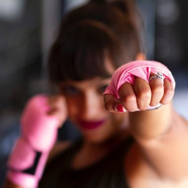 Woman fighting with pink boxing gloves